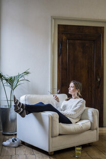 Woman sitting in armchair at home thinking - GIOF03618