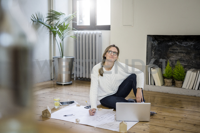 Woman sitting on the floor with blueprint and laptop - GIOF03621 - Giorgio Fochesato/Westend61