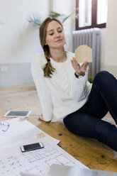 Woman sitting on the floor with blueprint looking at house model - GIOF03624