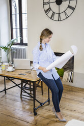 Woman in home office looking at blueprint - GIOF03630