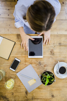Top view of woman at wooden desk with notebook, cell phone and tablet - GIOF03639