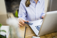 Close-up of woman at wooden desk with credit card and laptop - GIOF03642