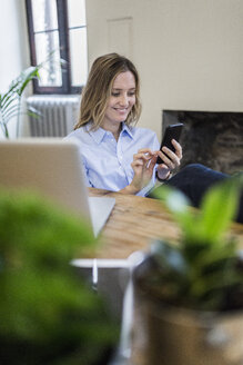 Smiling woman sitting at desk at home checking cell phone - GIOF03657