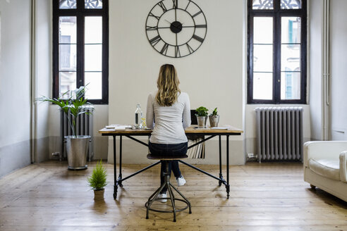 Rear view of woman sitting at desk at home under large wall clock - GIOF03663