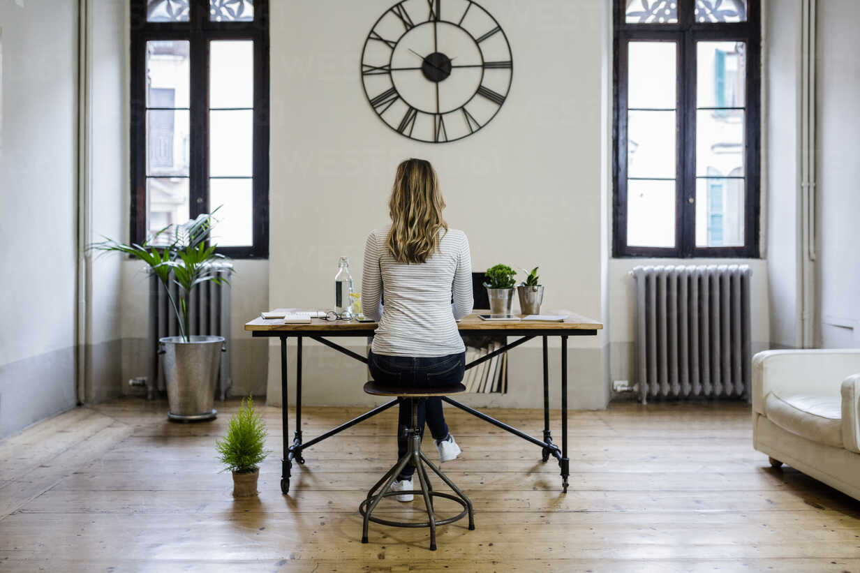 Rear view of woman sitting at desk at home under large wall clock - GIOF03663 - Giorgio Fochesato/Westend61