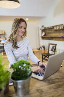 Smiling woman using laptop on wooden table at home - GIOF03666