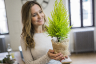 Smiling woman holding plant at home - GIOF03672