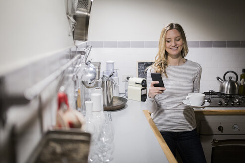 Smiling woman checking cell phone in kitchen - GIOF03678