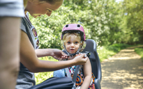 Little girl sitting on child seat for bicycle with her mother adjusting her helmet - DAPF00821