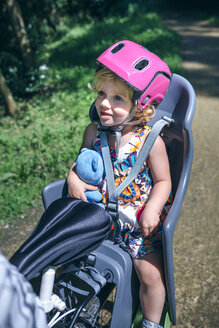 Lttle girl with helmet sitting on a child seat for bicycle - DAPF00830