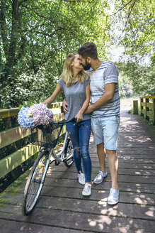 Couple with bicycle kissing on a wooden walkway in the countryside - DAPF00857