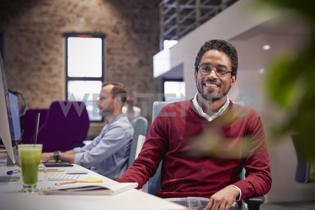 Young man sitting at desk in office, smiling - WESTF23783
