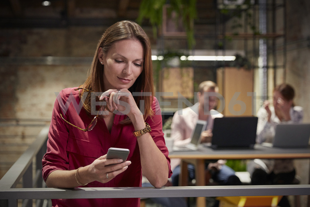 Businesswoman standing in office holding smartphone - WESTF23798