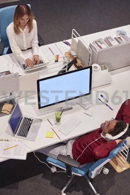 Colleagues working in modern office, man taking a break, listening music - WESTF23813