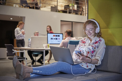 Young woman working in modern creative office, usine laptop and headphones - WESTF23855