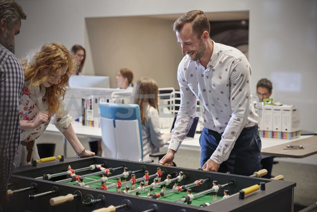 Business people in office taking a break, playing foosball - WESTF23864