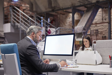 Businessman and woman working together in modern office - WESTF23873