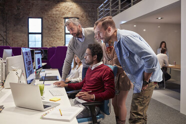 Colleagues looking over shoulder of young man working in modern office - WESTF23882