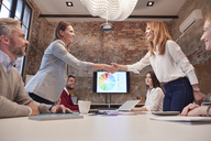 Two businesswomen shaking hands at a presentation - WESTF23885