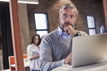 Mature man sitting at laptop, thinking - WESTF23888