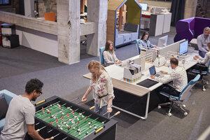 Business people in office taking a break, playing foosball - WESTF23903