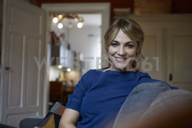 Portrait of smiling woman relaxing on couch at home - RBF06170 - Rainer Berg/Westend61