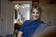 Portrait of smiling woman relaxing on couch at home - RBF06170