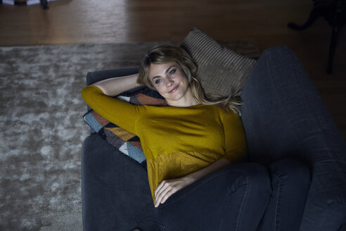 Portrait of smiling woman relaxing on couch at home - RBF06176