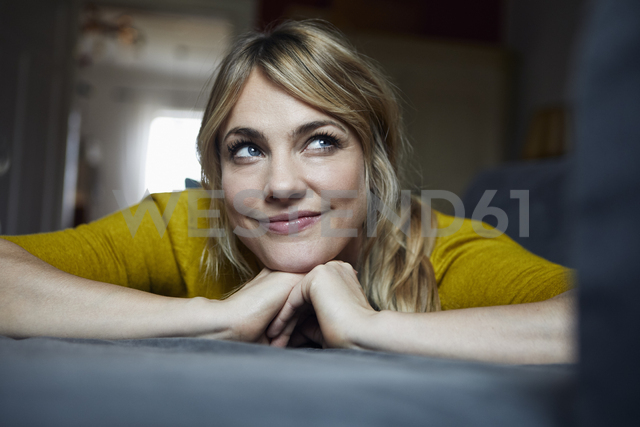 Portrait of woman lying on the couch at home thinking - RBF06182