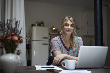 Portrait of smiling woman with laptop sitting at table in the kitchen - RBF06191