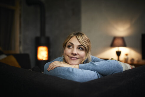 Portrait of smiling woman relaxing on couch at home in the evening - RBF06200