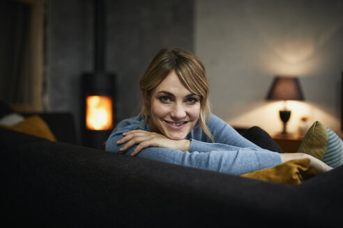Portrait of smiling woman relaxing on couch at home in the evening - RBF06203
