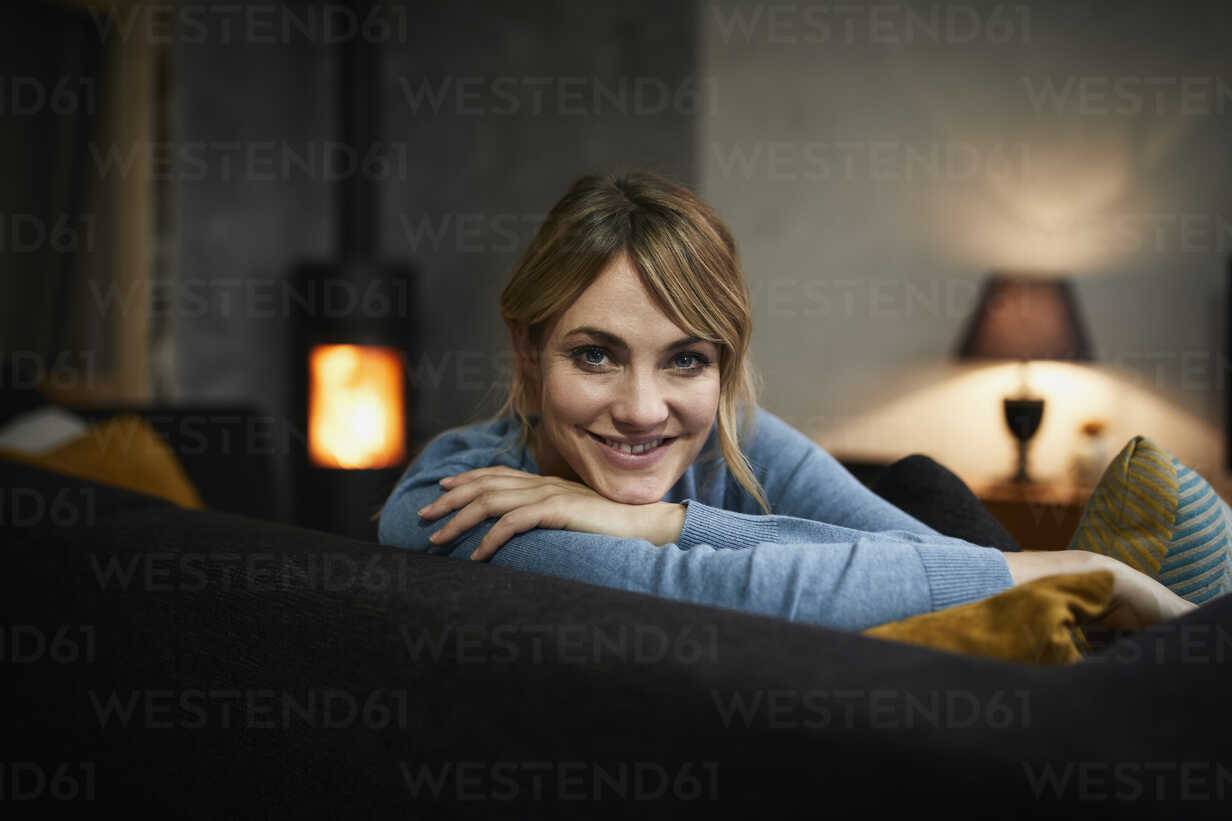 Portrait of smiling woman relaxing on couch at home in the evening - RBF06203 - Rainer Berg/Westend61