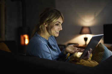 Portrait of smiling woman using tablet at home in the evening - RBF06206
