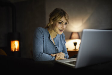 Portrait of amazed woman using laptop at home in the evening - RBF06209