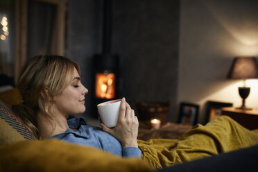 Smiling woman with cup of coffee relaxing on couch at home in the evening - RBF06212