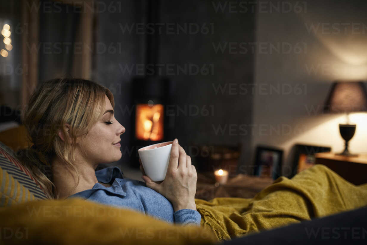 Smiling woman with cup of coffee relaxing on couch at home in the evening - RBF06212 - Rainer Berg/Westend61