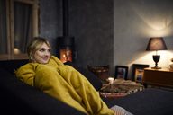 Portrait of smiling woman relaxing on couch at home in the evening - RBF06215