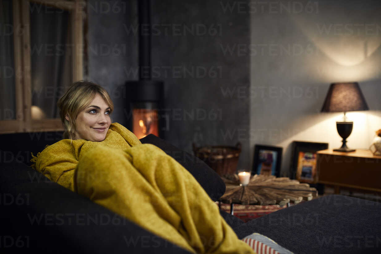 Portrait of smiling woman relaxing on couch at home in the evening - RBF06215 - Rainer Berg/Westend61