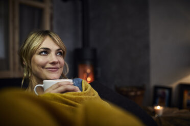 Portrait of smiling woman with cup of coffee relaxing on couch at home in the evening - RBF06218