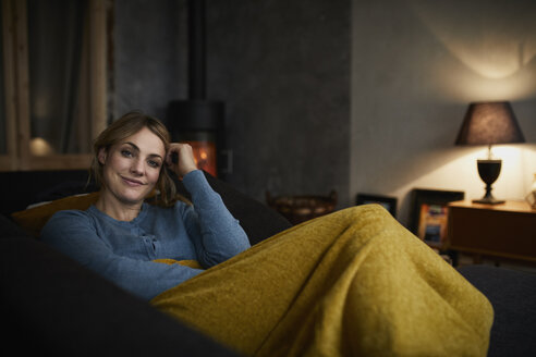 Portrait of happy woman relaxing on couch at home in the evening - RBF06221
