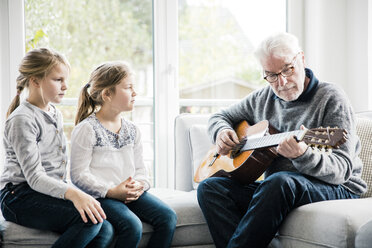 Two girls sitting on sofa listening to grandfather playing guitar - MOEF00519