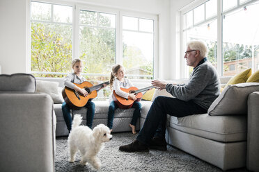 Two girls on sofa playing guitar with grandfather and dog - MOEF00522