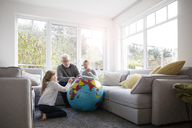 Two girls and grandfather with globe in living room - MOEF00531