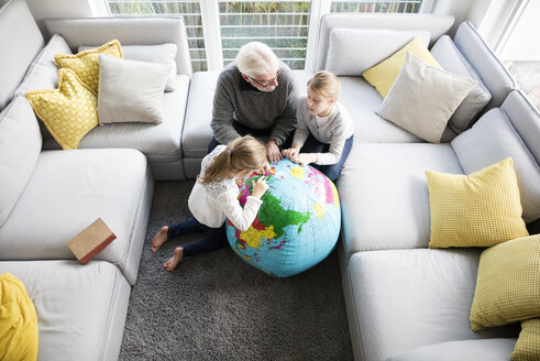 Two girls and grandfather with globe in living room - MOEF00534