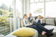 Grandfather talking to two girls on sofa in living room - MOEF00537