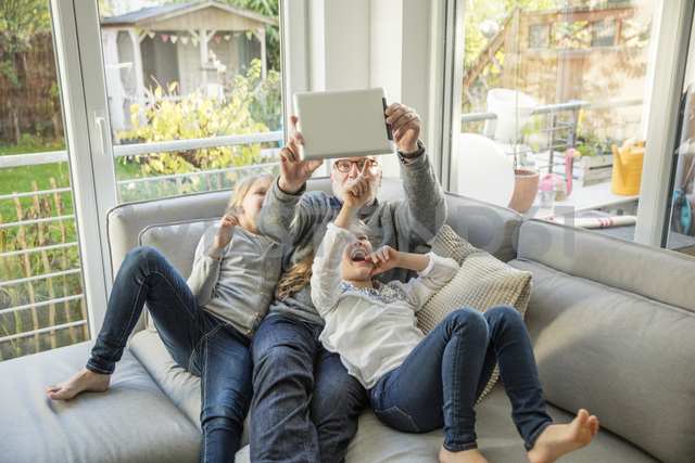 Two happy girls and grandfather on sofa taking a selfie with tablet - MOEF00540