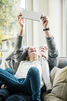Two happy girls and grandfather on sofa taking a selfie with tablet - MOEF00543
