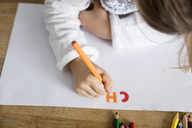 Girl writing letters on paper with colored pencil - MOEF00549