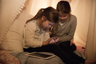 Two girls with cell phone and tablet in children's room - MOEF00555